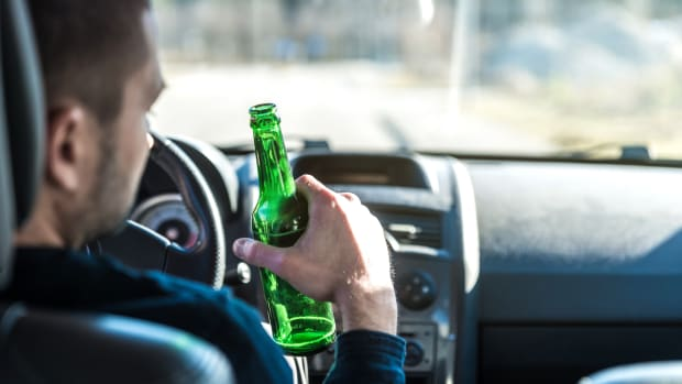 Mann trinkt Bier beim Autofahren