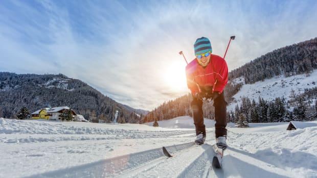 Mann mit Skiern in der Langlaufloipe, die Sonne scheint und der Schnee glitzert