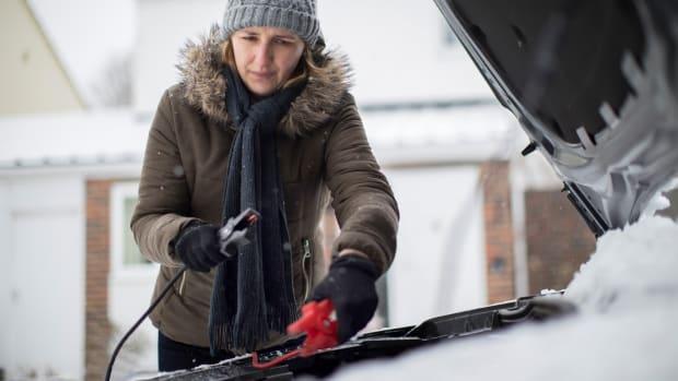 Frau im Winter gibt Starthilfe mit Überbrückungskabel