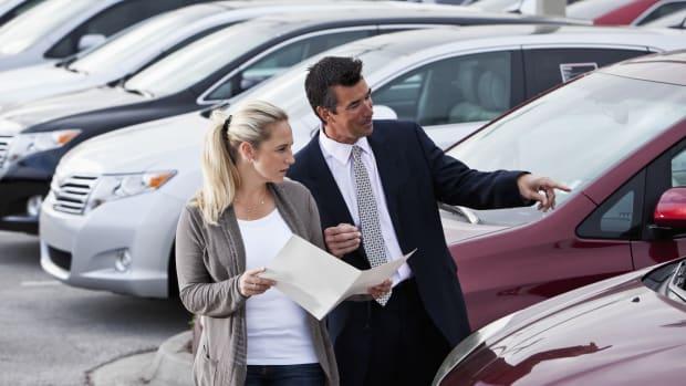 Eine Frau beim Gebrauchtwagenhändler