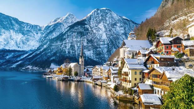 Ein verschneites Dorf am See direkt an den Bergen