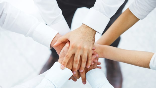 Teammitglieder legen ihre Hände zusammen