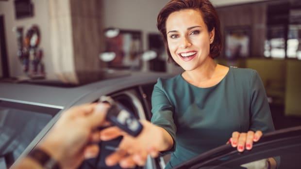 Eine Frau nimmt einen Autoschlüssel entgegen
