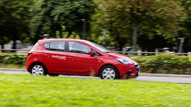 Rotes Auto von stadtmobil Carsharing fährt durch die Stadt