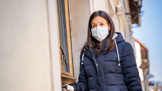 Frau mit Mundschutz öffnet Haustür