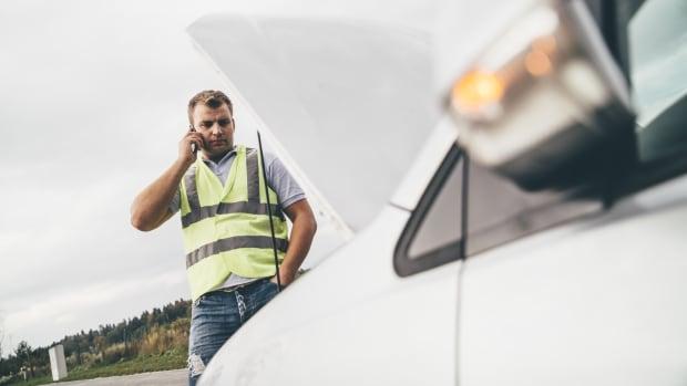 Mann mit Warnweste telefoniert und schaut dabei in seinen Motor