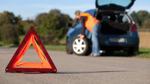 Eine Frau mit Warnweste wechselt den Reifen an ihrem Auto