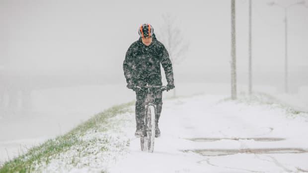 Fahrradfahrer fährt auf einem verschneiten Radweg
