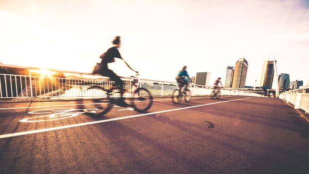 Fahrradfahrer fahren bei Sonnenuntergang auf einem Radweg