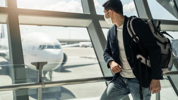 Eine Frau mit Corona Maske schaut auf Flugzeuge am Flughafen