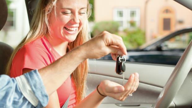 Junge Frau nimmt einen Autoschlüssel entgegen