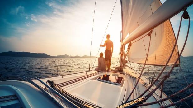 Mann und Frau stehen am Bug eines Segelschiffs