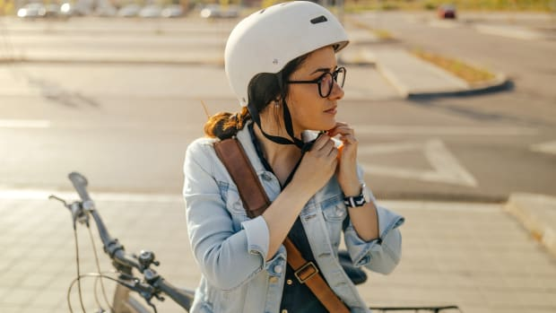 Frau schließt ihren Fahrradhelm