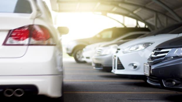 Auto fährt an parkenden Fahrzeugen vorbei