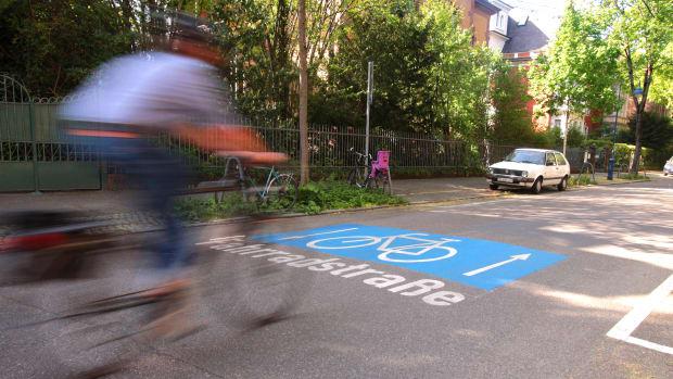 Mann fährt mit seinem Fahrrad auf einer Fahrradstraße