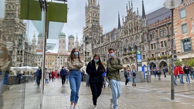 Fußgänger mit Mundschutz auf dem München Marienplatz