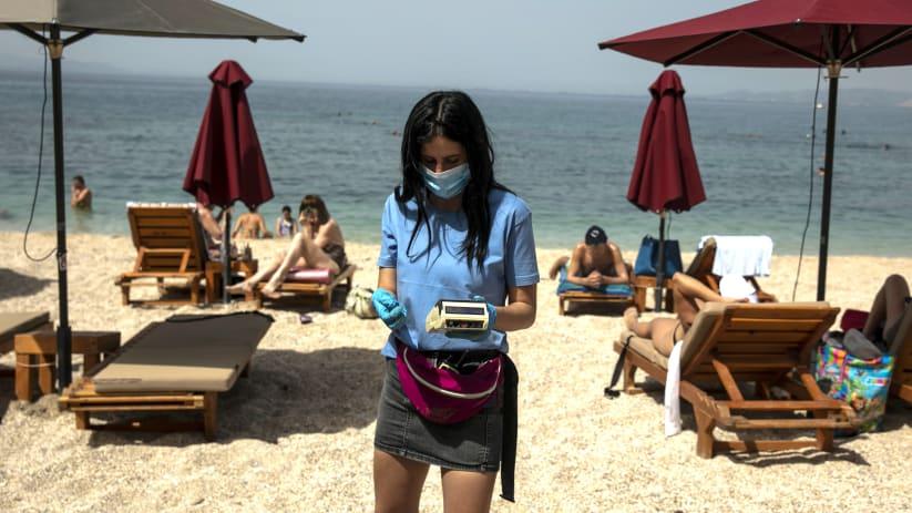 Eine Kellnerin mit Maske steht an einem griechischen Strand zwischen Liegen und Sonnenschirmen.