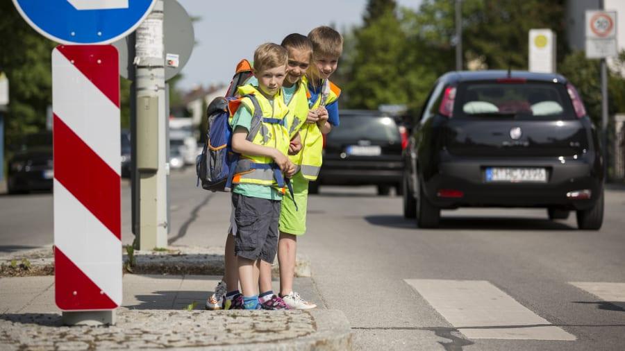 Kinder überqueren Zebrastreifen auf ihrem Schulweg