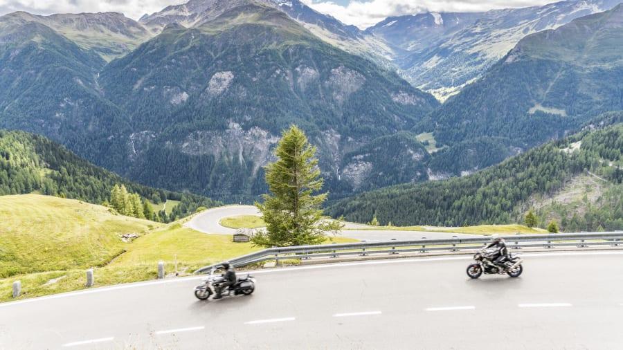 zwei Motorradfahrer auf einer Strasse durch die Alpen