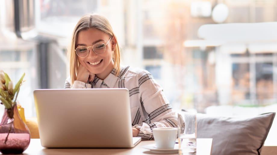 Eine Frau sitzt im Café am Laptop