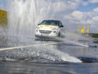 ADAC Opel Adam fährt auf nasser Fahrbahn durch Wasserfontäne beim Fahrsicherheitstraining