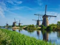 Windmühlen am Rande eines Flusses in Holland