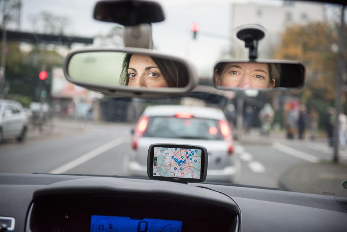 Frauen blicken während Fahrstunde in den Rückspiegel