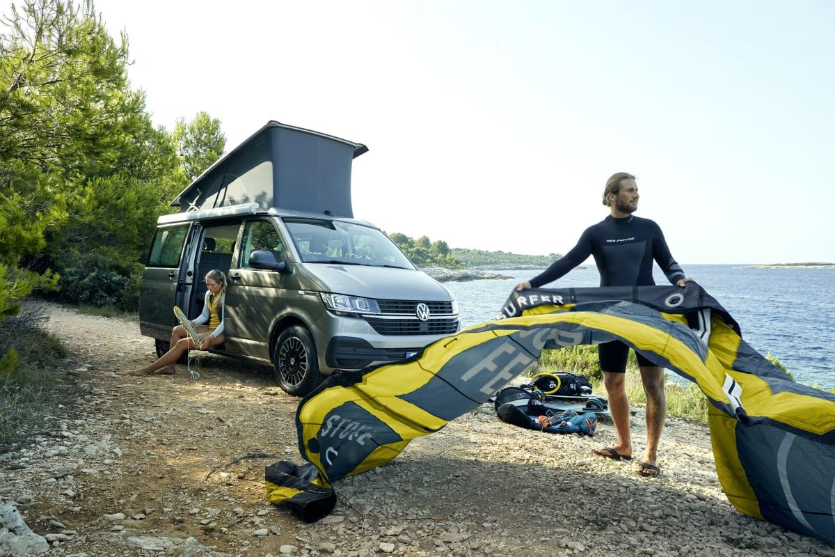 Zwei junge Menschen beim Camping im VW California