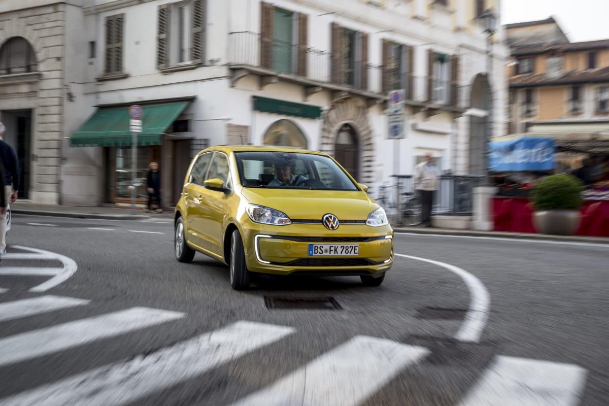 gelber VW e-Up fahrend von vorne