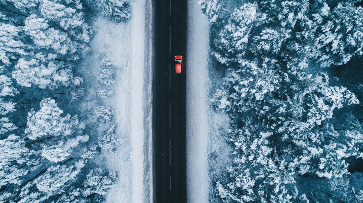 Rotes Auto fährt auf einer Strasse in einer verschneiten Landschaft, betrachten aus der Vogelperspektive