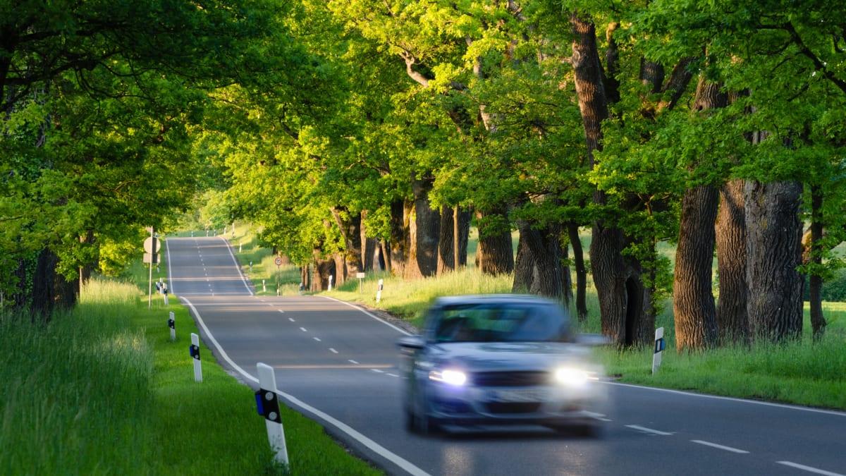 Auto mit eingeschalteten Scheinwerfern fährt auf Landstrasse