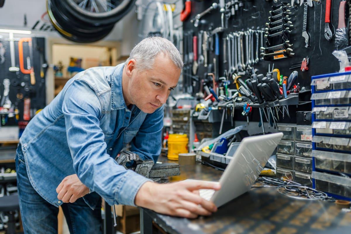 Mechaniker lehnt über dem Laptop in einer Autowerkstatt