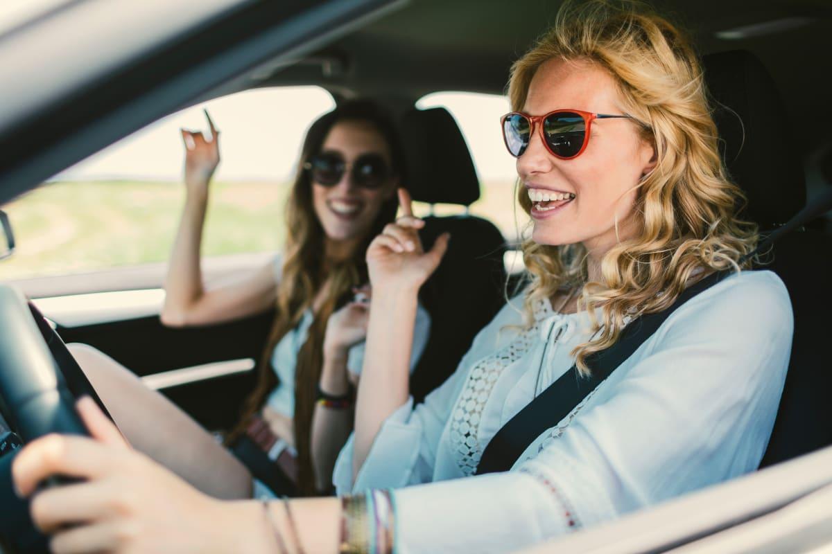 Zwei junge Frauen hören im Auto Musik