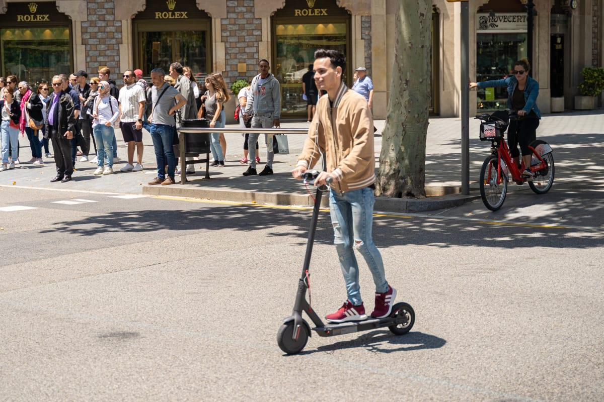 Mann fährt mit Elektro-Scooter auf einer Straße in Barcelona.