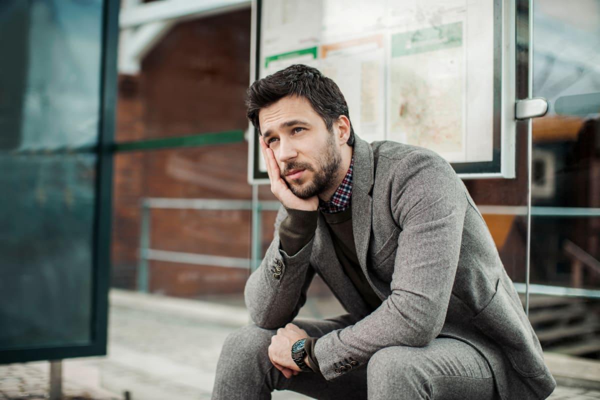 Mann wartet an Bushaltestelle auf den Bus