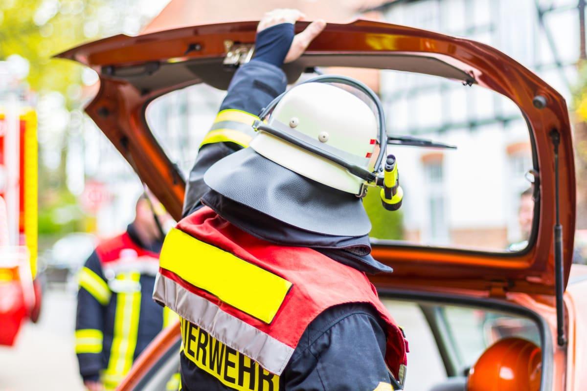 Feuerwehrmann öffnet Kofferraum eines Autos