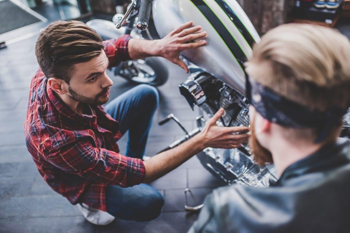 Mann berät Kunde beim Motorradkauf