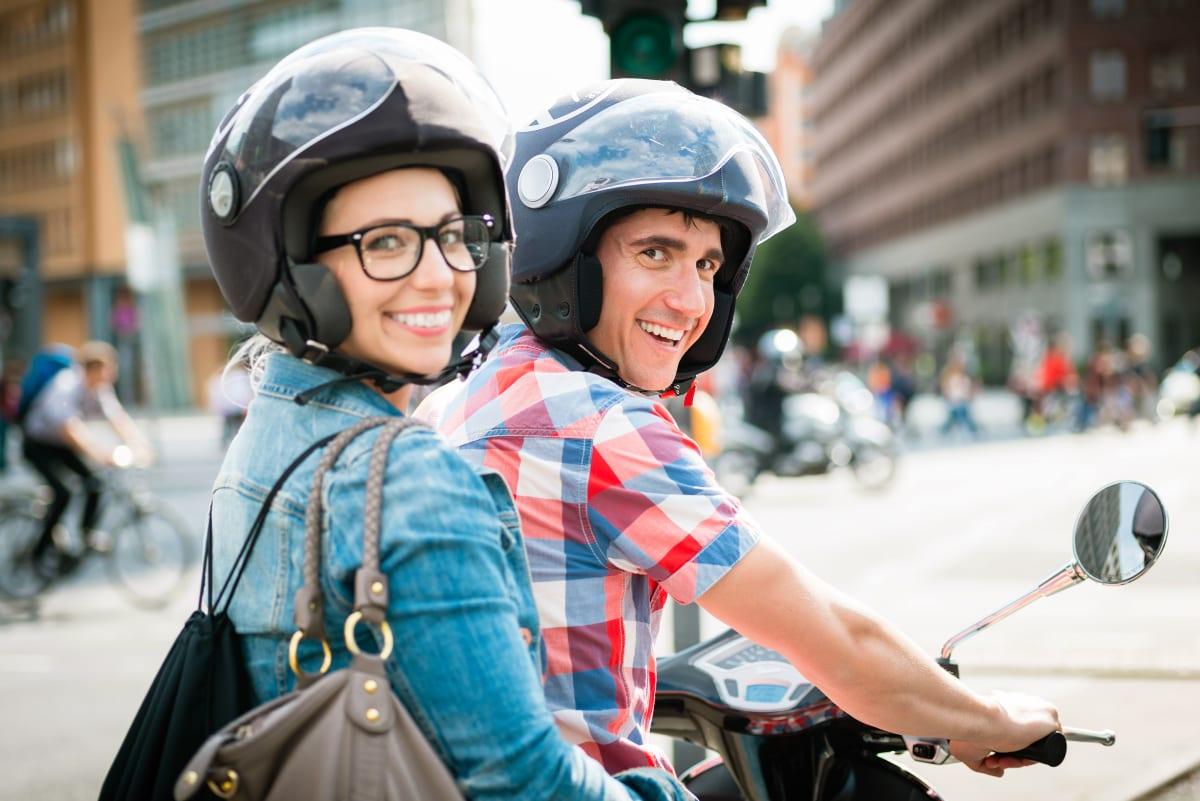 -zwei junge Rollerfahrer fahrend lachend in Berlin