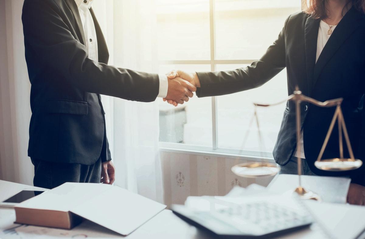 Mann und Frau schütteln Hände nach erfolgreicher Verhandlung