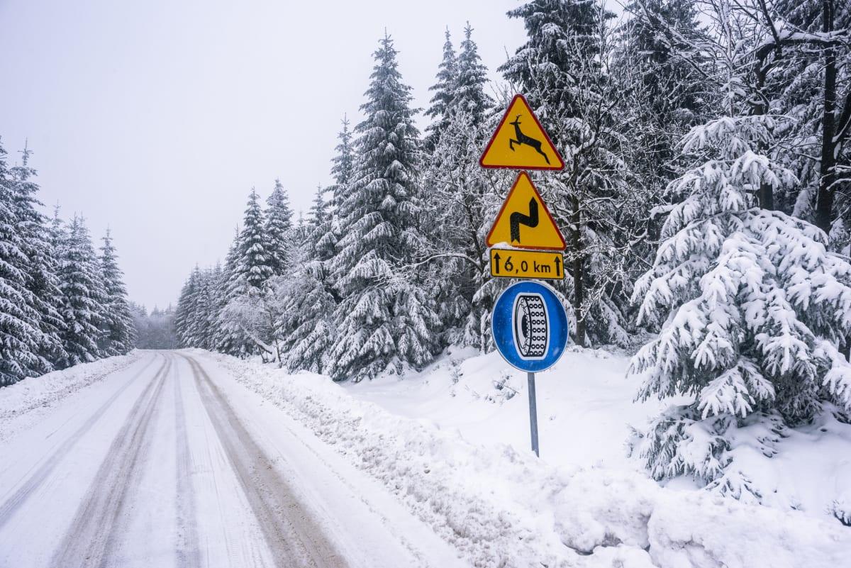 Verschneite Strasse mit Verkehrsschild