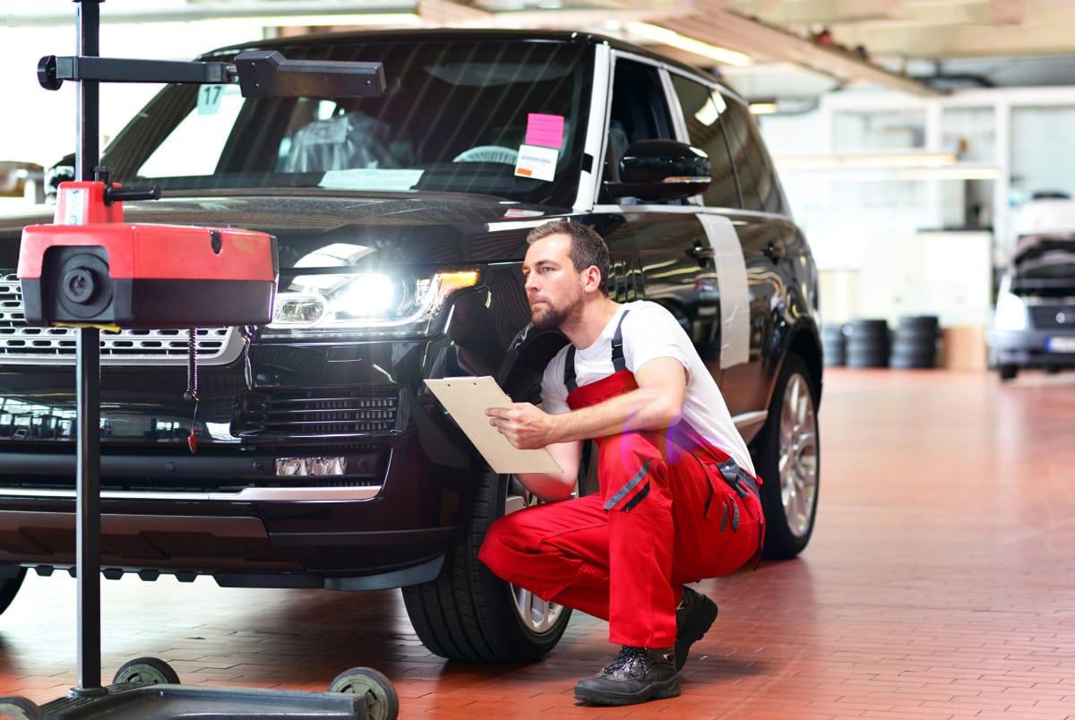 Mechaniker macht einen Lichttest in einer Werkstatt