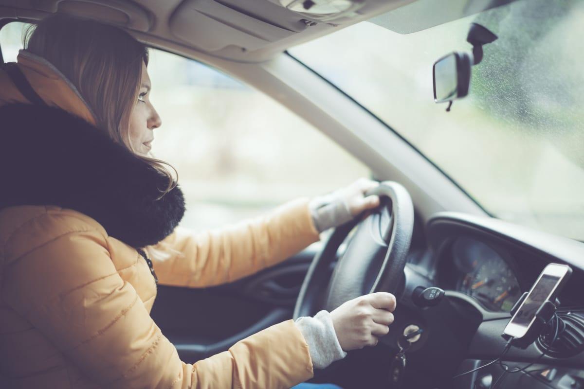 Frau fährt mit dicker Jacke im Winter Auto