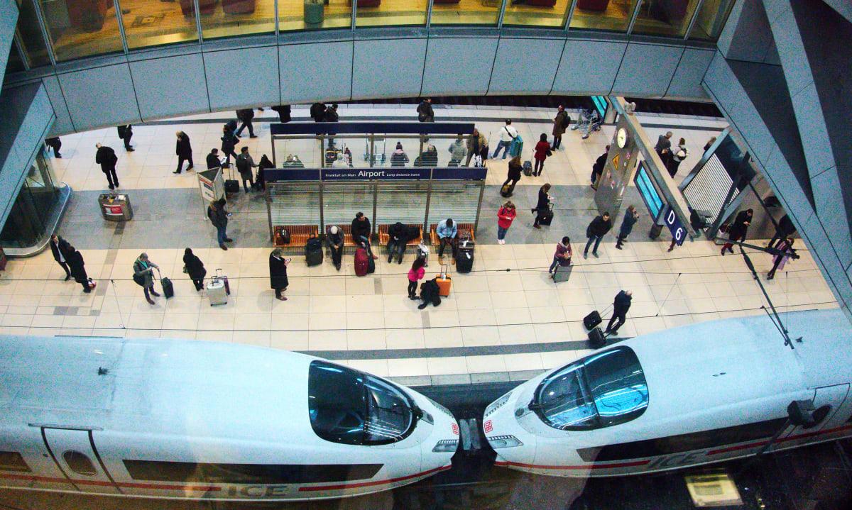 Reisende warten am Bahnsteige des Flughafen Frankfurts auf den Zug