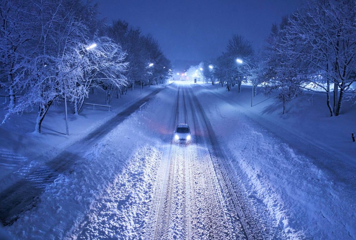 ein Auto fährt Nachts auf verschneiter Strasse