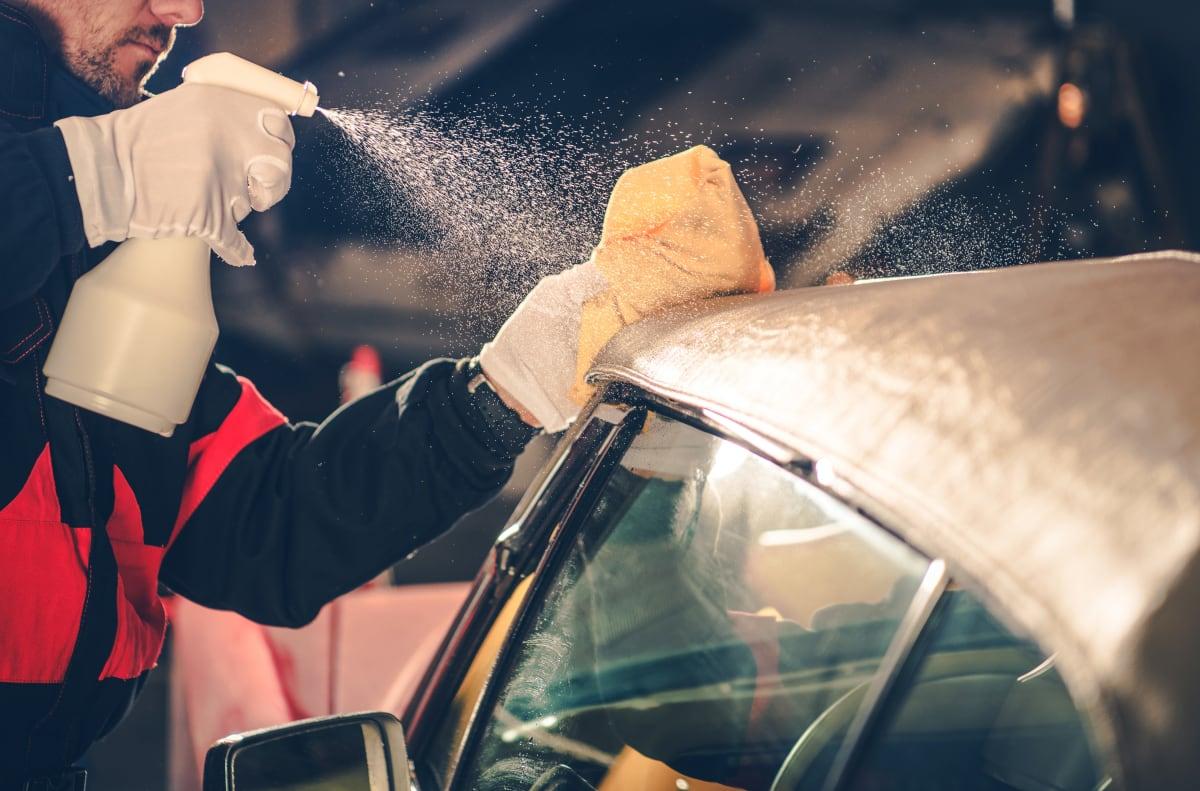 Mann Sprüht Flüssigkeit auf ein Cabrio Dach