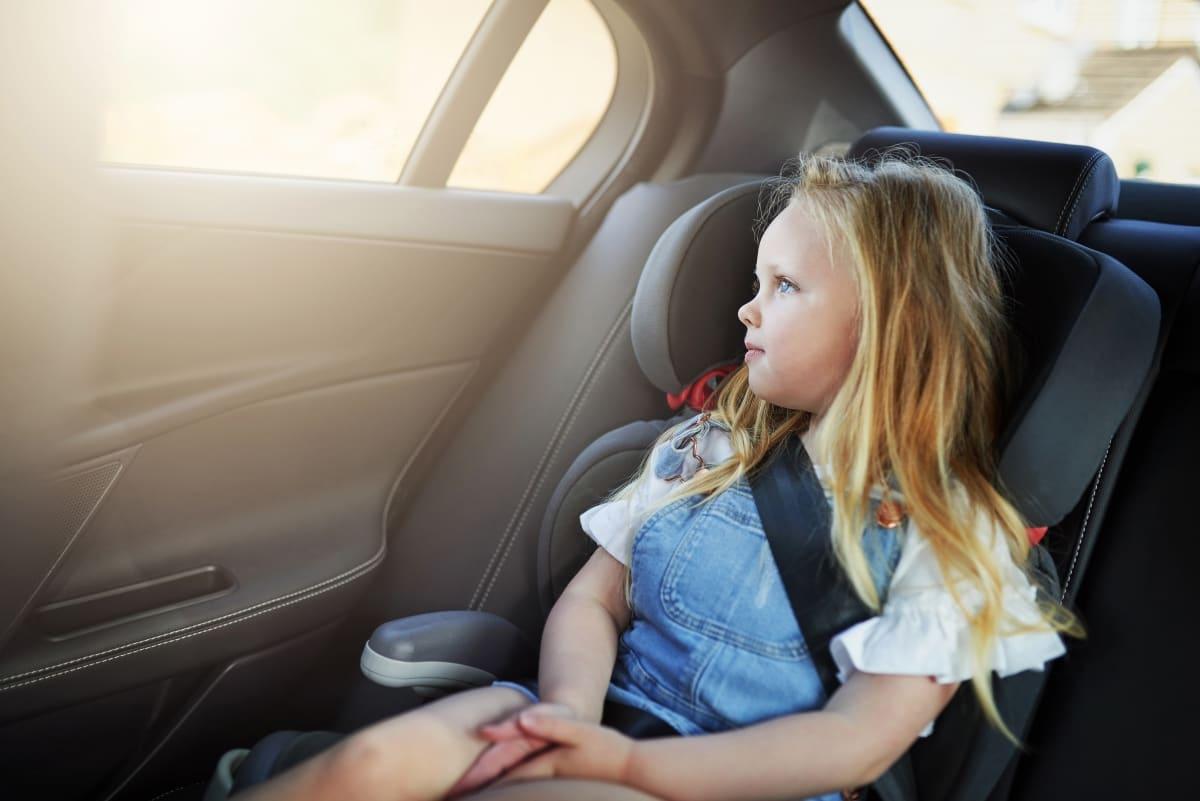 Mädchen sitzt angeschnallt im Kindersitz im Auto