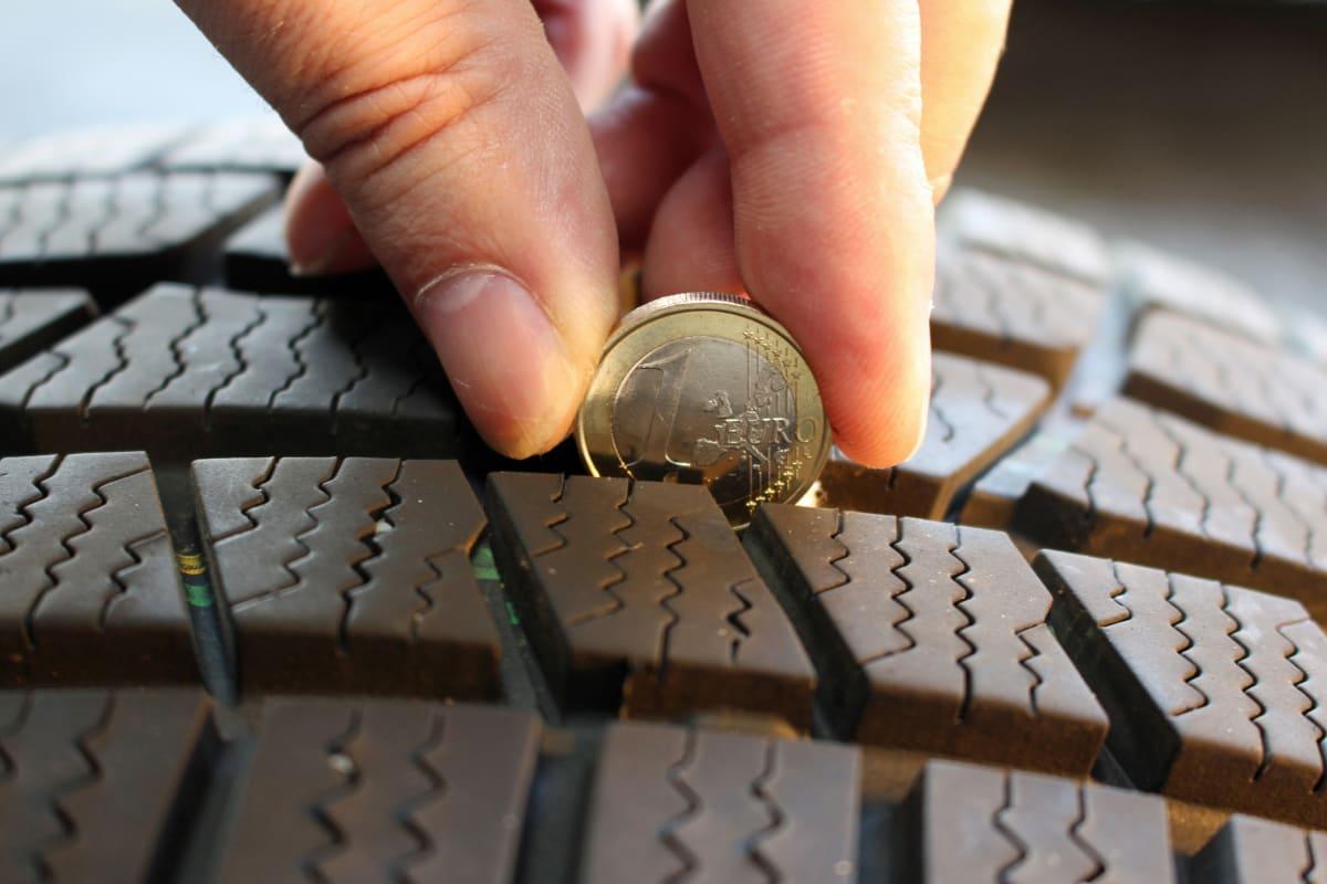 Mann misst mit Geldstück die Profiltiefe eines Reifens