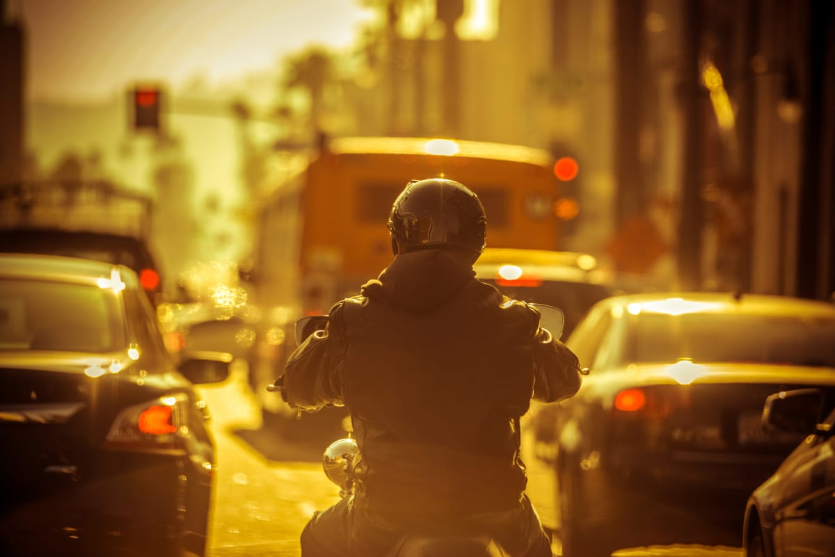Motorradfahrer schlängelt sich durch Stau
