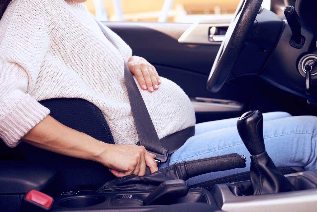 Schwangere Frau schnallt sich in Auto an