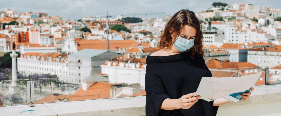 Junge Frau mit Maske schaut auf einen Stadtplan in Lissabon